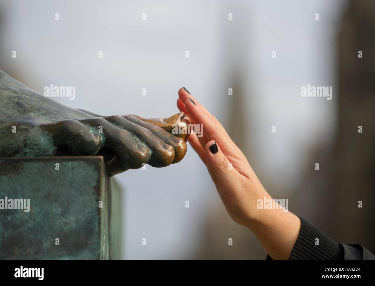 Tourist touches the big toe on the statue of philosopher David Hume that sits outside the High Court on Edinburgh's - Stock Image