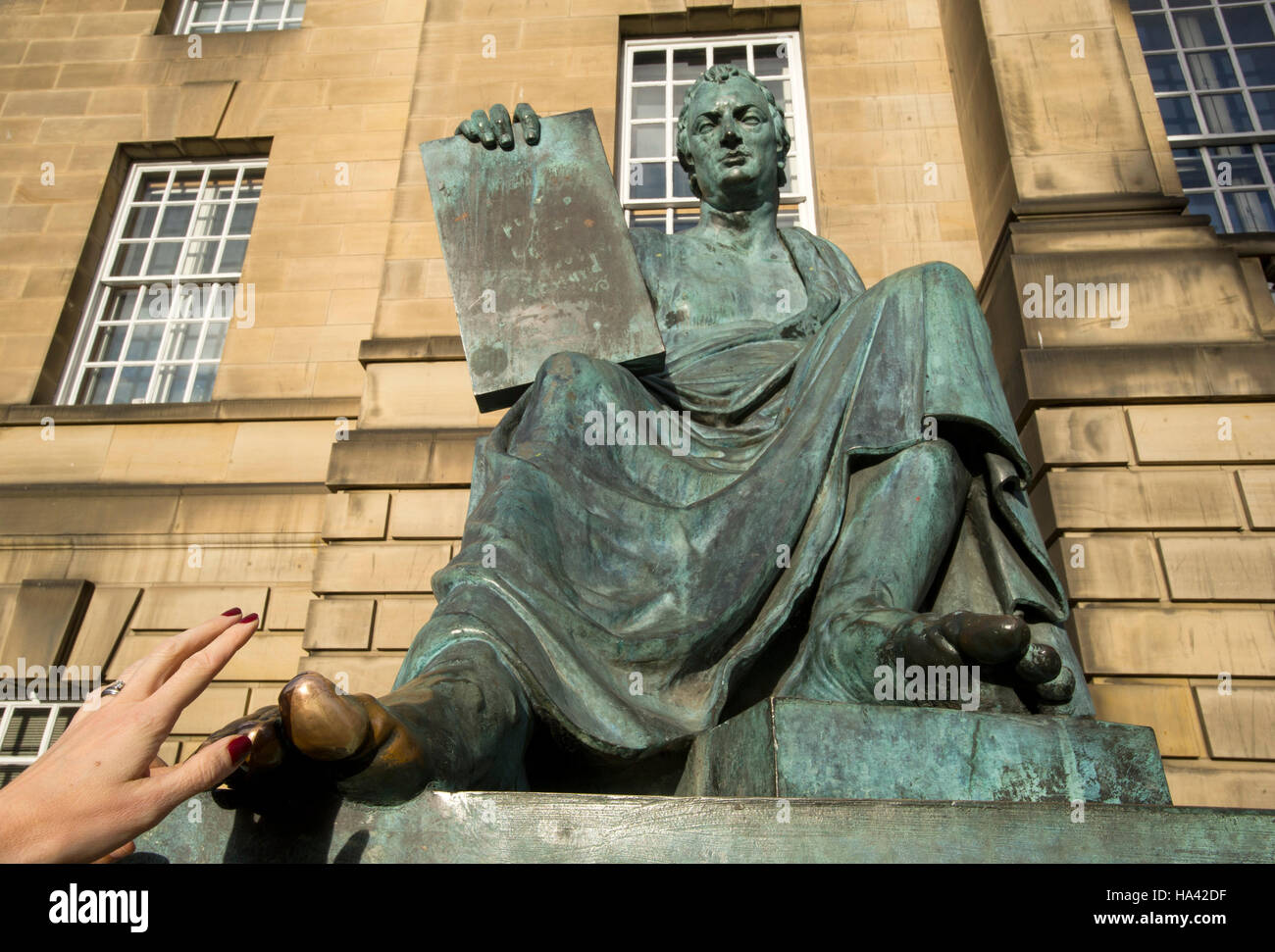 A tourist touches the big toe of the statue of philosopher David Hume outside the High Court on Edinburgh's - Stock Image