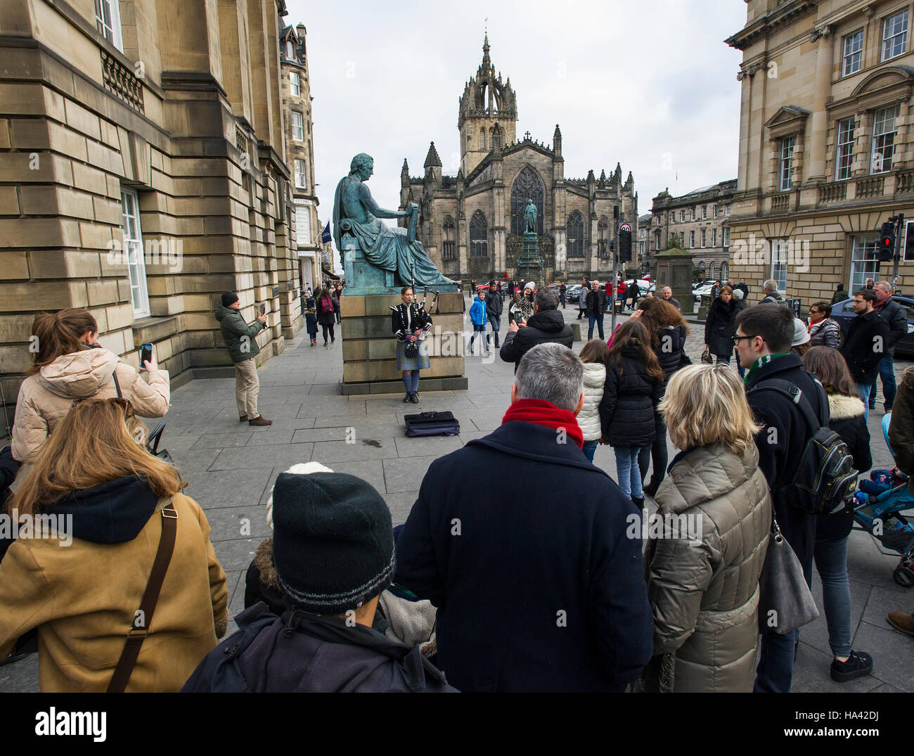 Tourists look at the statue of philosopher David Hume (1711 -1776) on Edinburgh's Royal Mile. - Stock Image