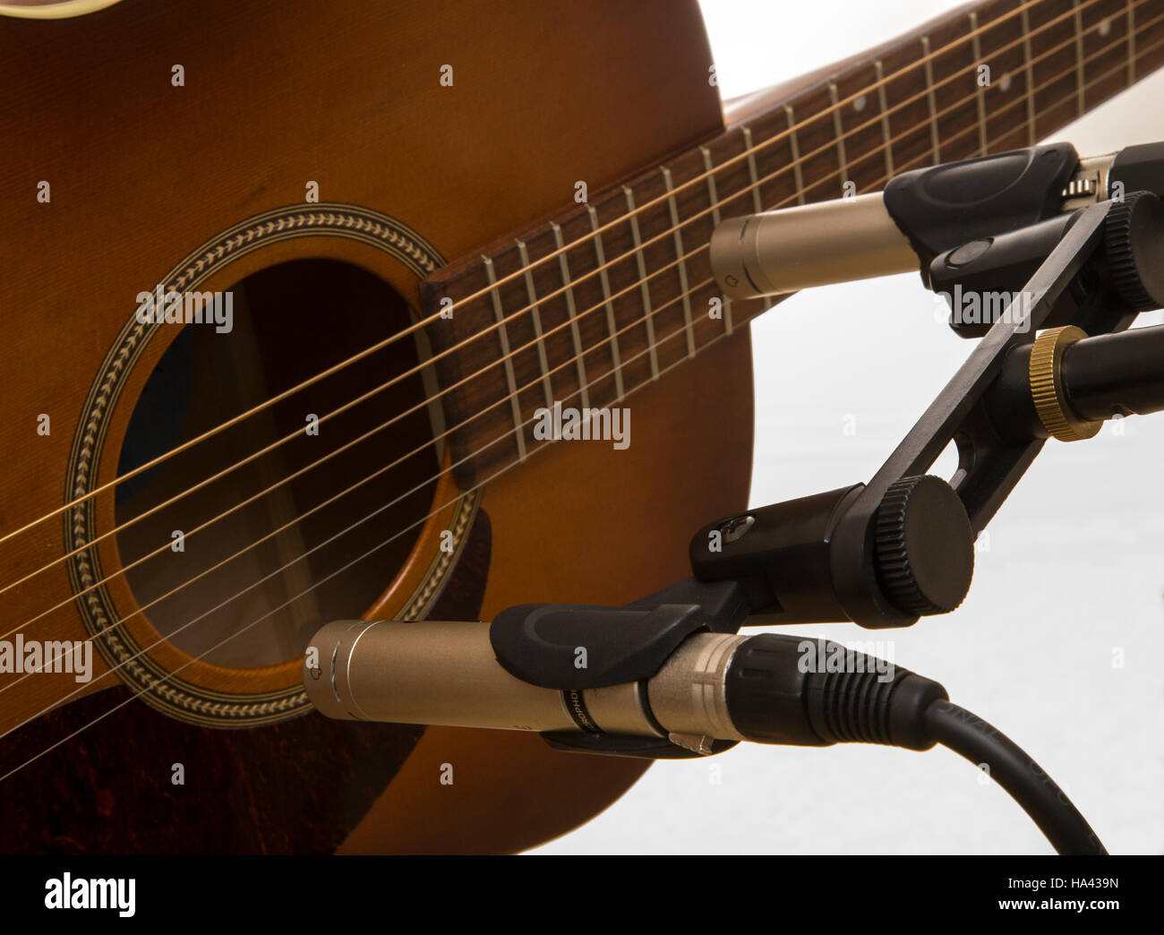 Recording a guitar using a matched pair of condenser instrument microphones, one set to the neck, the other toward - Stock Image