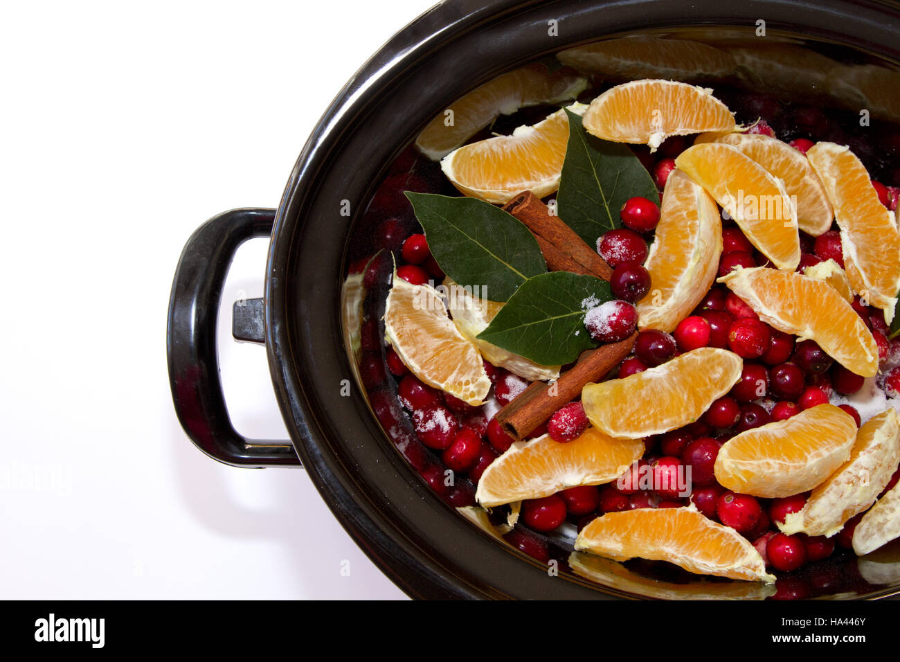 Homemade cranberry sauce ingredients of cinnamon, oranges, cranberries, bay leaf simmering in a crock pot isolated - Stock Image