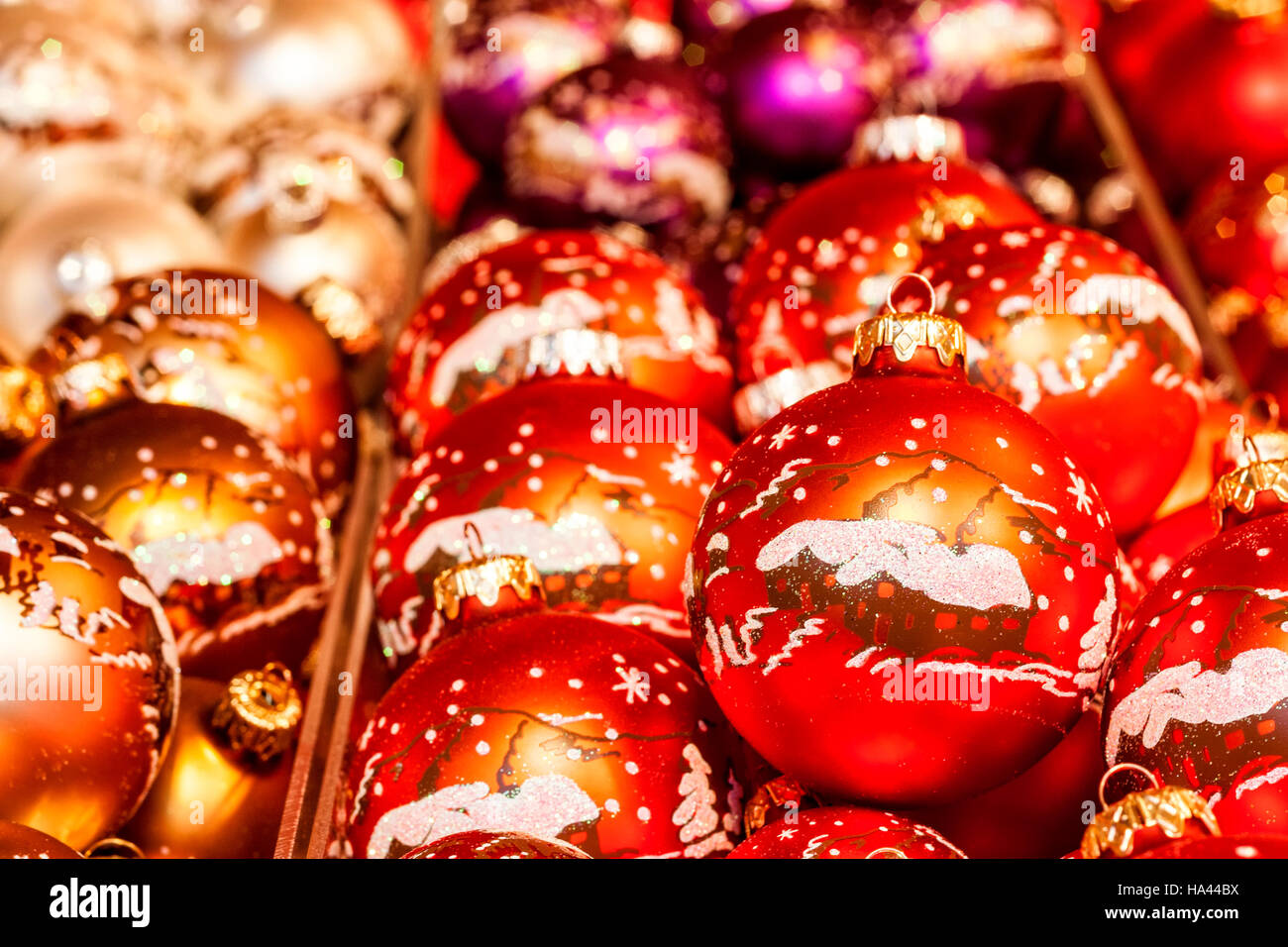 Traditional christmas balls with decorative ornaments with beautiful winter scene with houses, hills, stars and - Stock Image