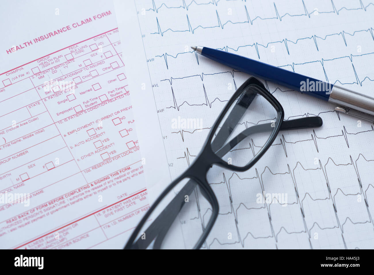 Health insurance claim form with pen and glasses - Stock Image
