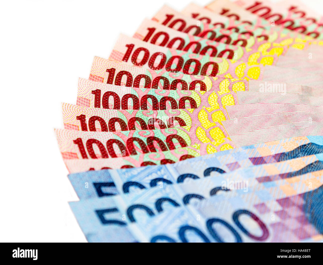 Piles of Indonesian Rupiah (IDR) banknotes on the white background. - Stock Image