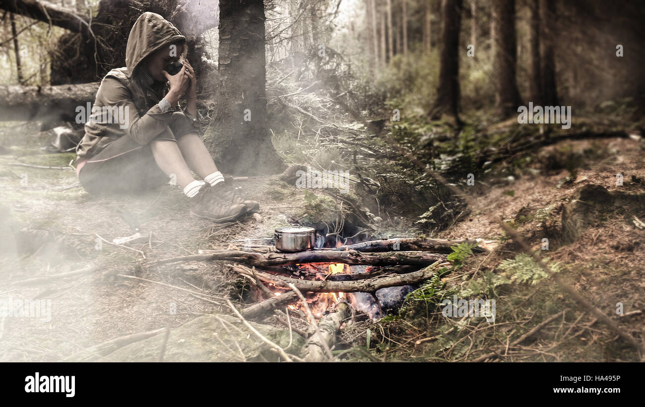 young female drinking tea by the fire in woods - Stock Image