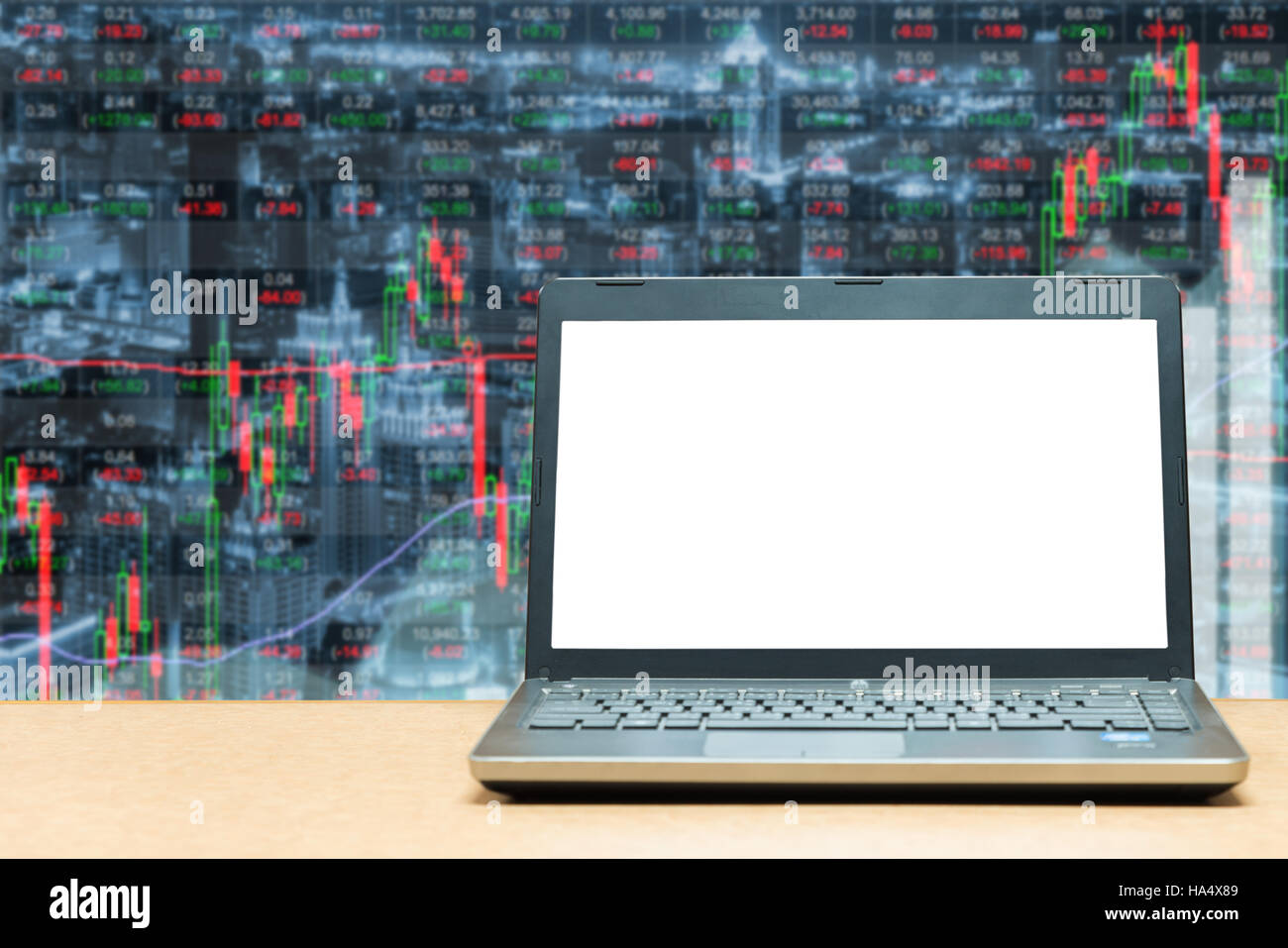 Laptop with blank screen on table with stock exchange market business trading graph. Business marketing trade concept. - Stock Image