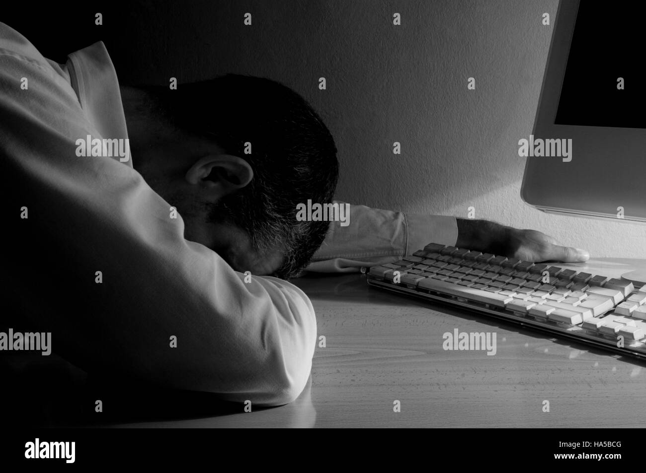 Depressed man at the computer. Black and white. - Stock Image
