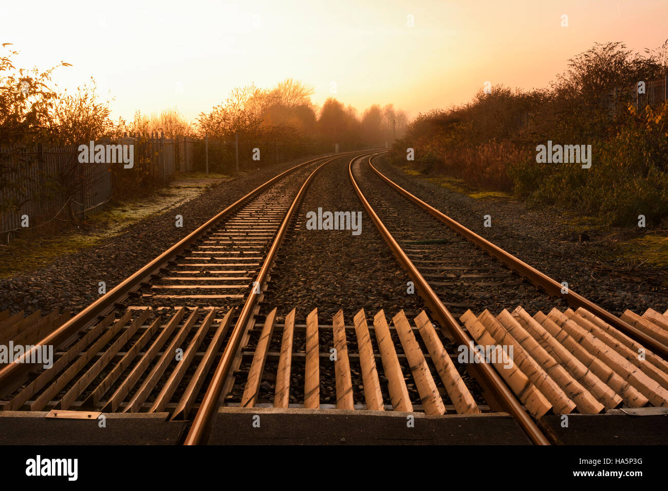 Railway lines curving off into the mist. - Stock Image
