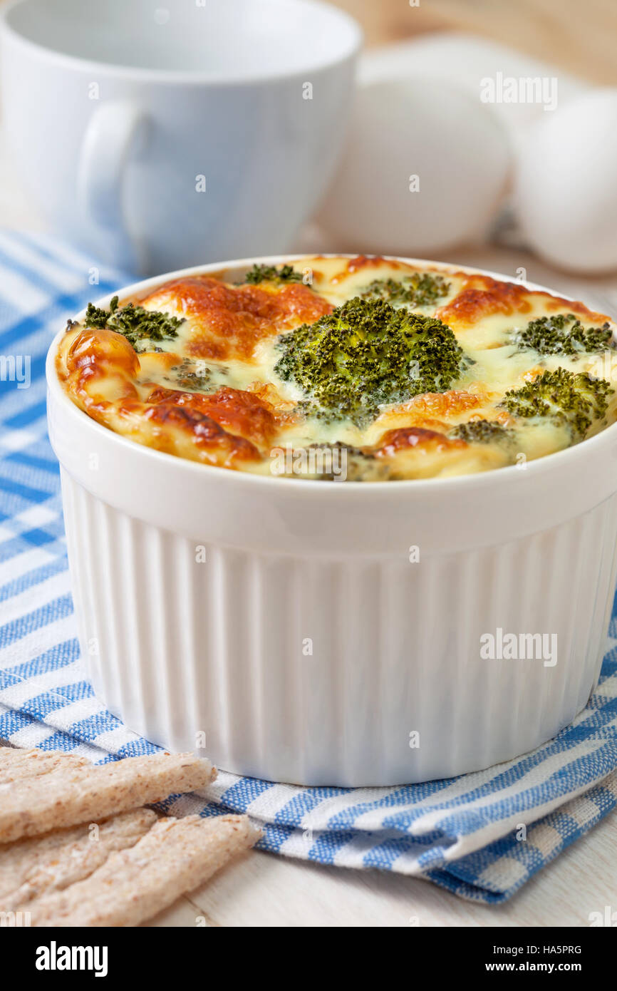 Healthy dietary breakfast. Broccoli casserole with eggs, cheese in a white bowl, crisp bread on the white wooden - Stock Image