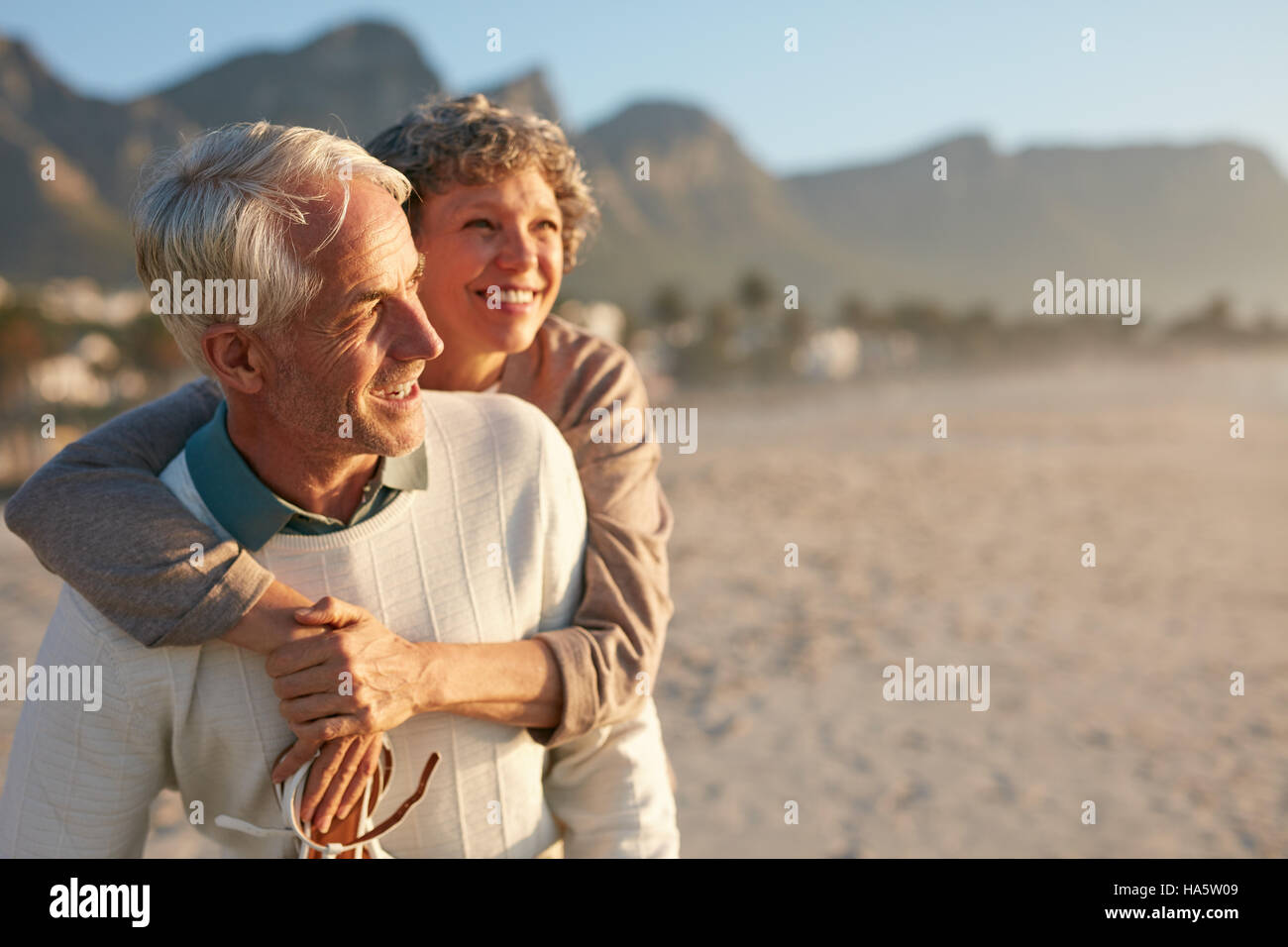 Portrait of happy mature man carrying his beautiful wife on his back at the beach. Senior couple enjoying their - Stock Image
