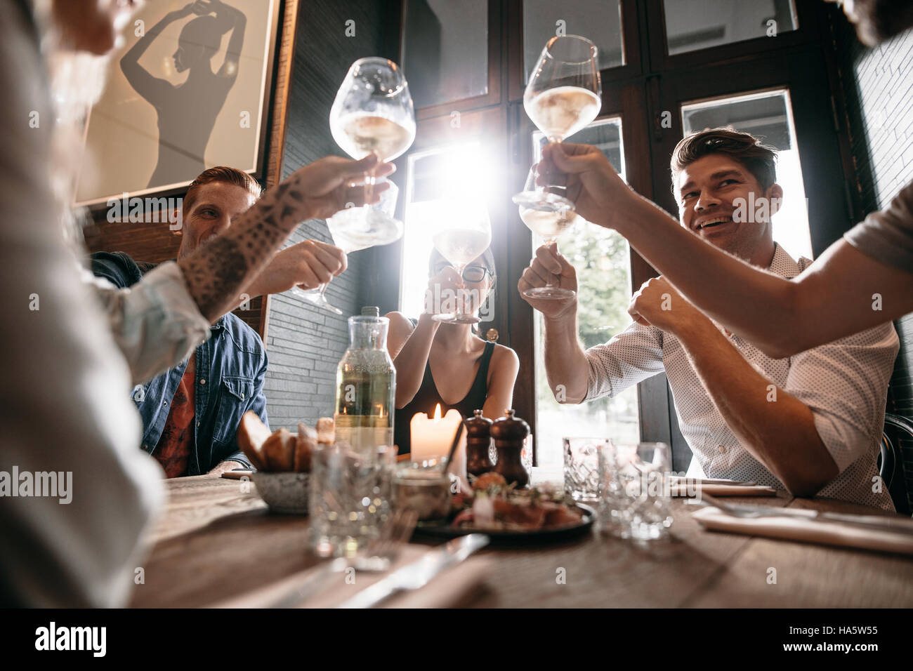 Group of young people making a toast at restaurant. Men and women sitting at a table in cafe and toasting wine. - Stock Image