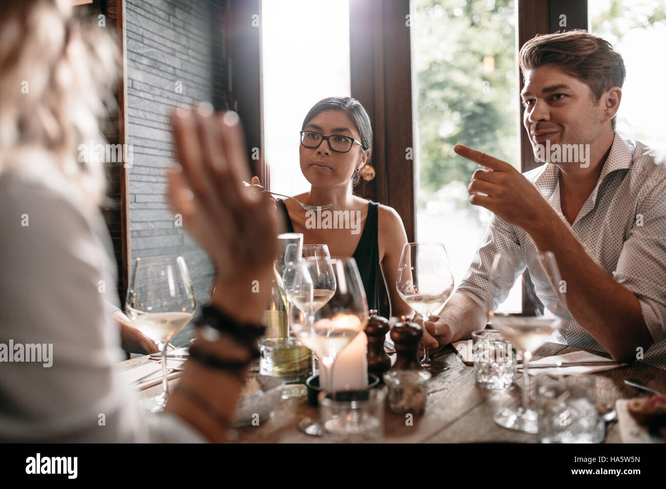 Group of friends meeting at restaurant for dinner. Young men and women having evening meal at cafe. - Stock Image