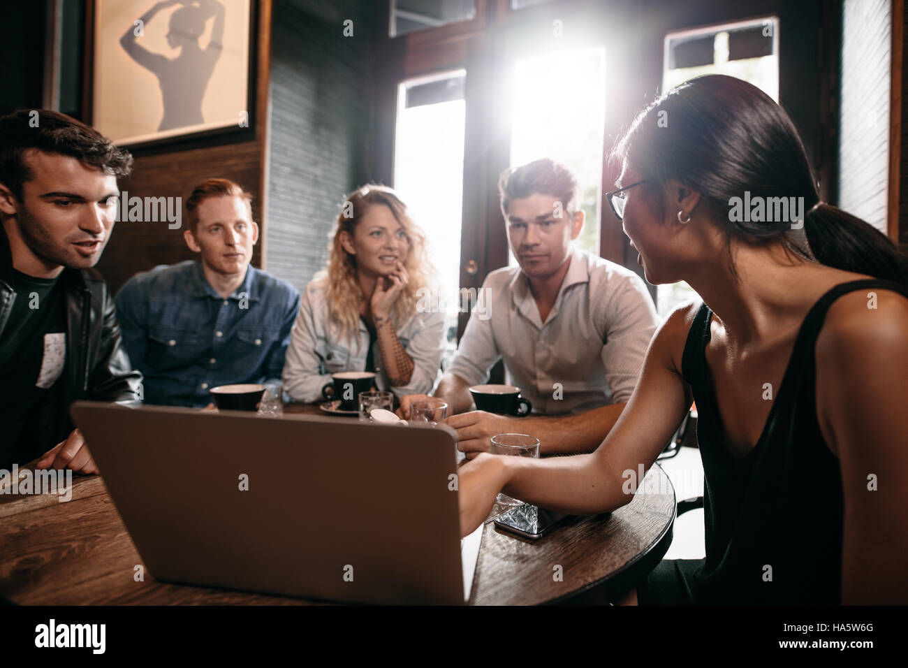 Smiling friends spending their time in coffee shop and discussing something while looking at laptop. Woman showing - Stock Image