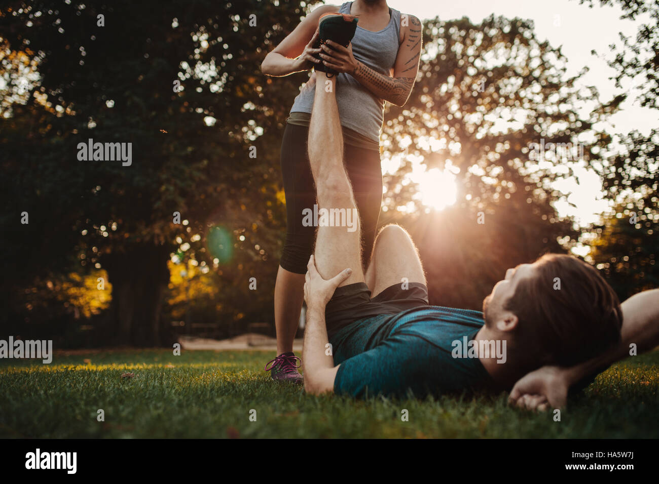 Young man having a strain and being stretched by female trainer. Woman stretches man's leg, muscle spasm after - Stock Image