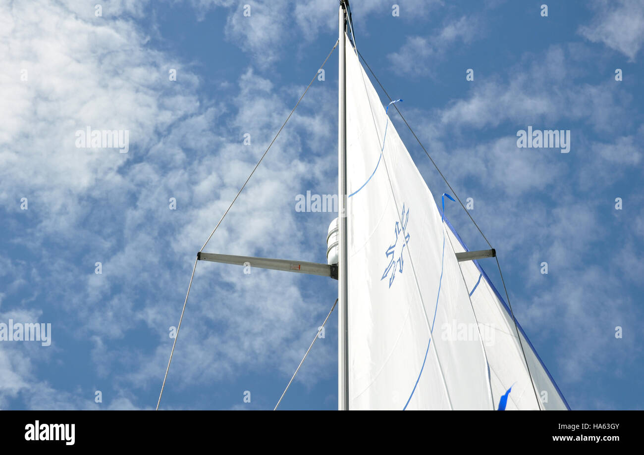 A yacht mainsail against a blue sky with white clouds - Stock Image