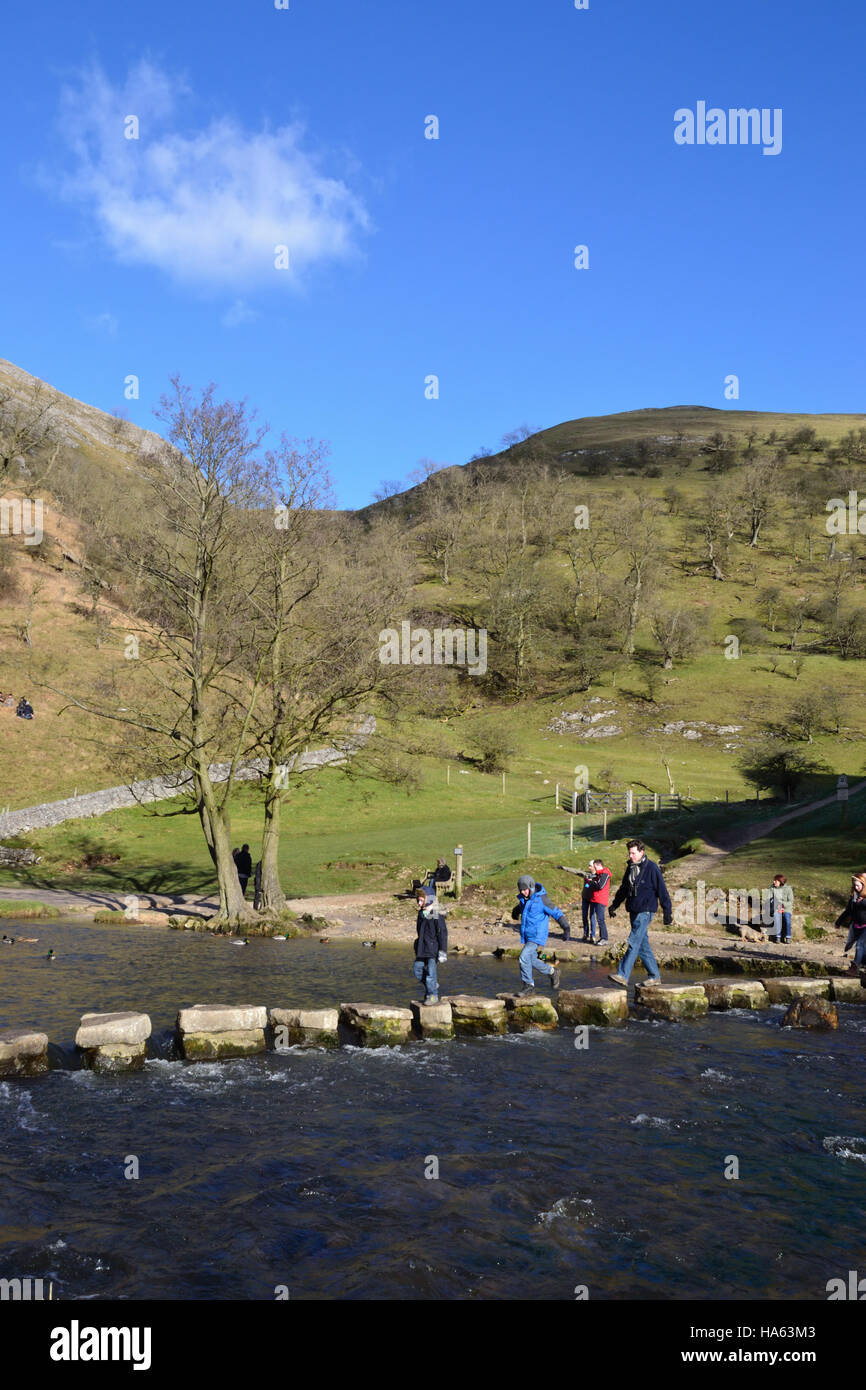 A family crossing the stepping stones at Dovedale in the Derbyshire Peak District. Stock Photo