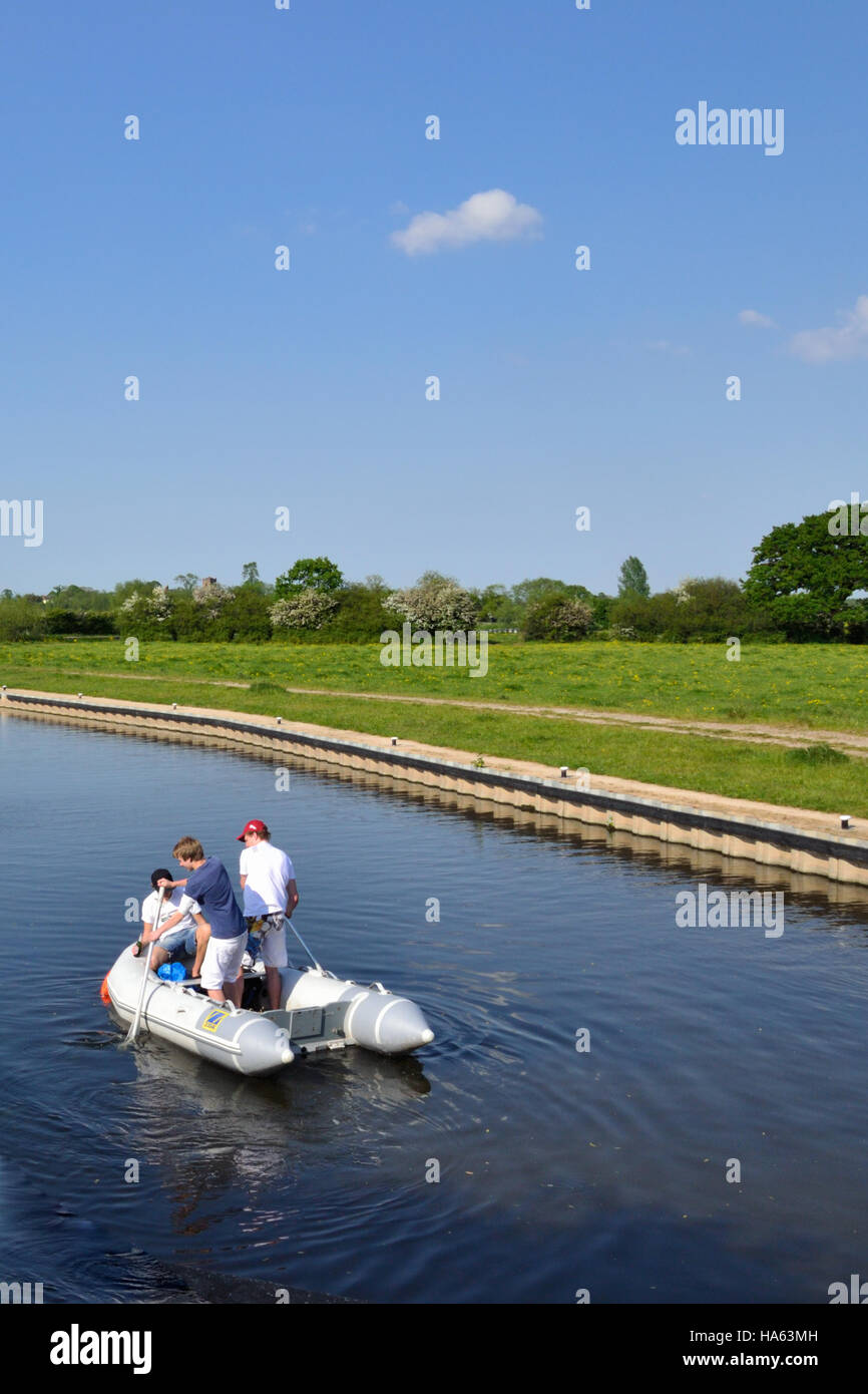 Three male teenagers having fun in a rubber dingy on the Trent & Mersey Canal near Alrewas. Stock Photo