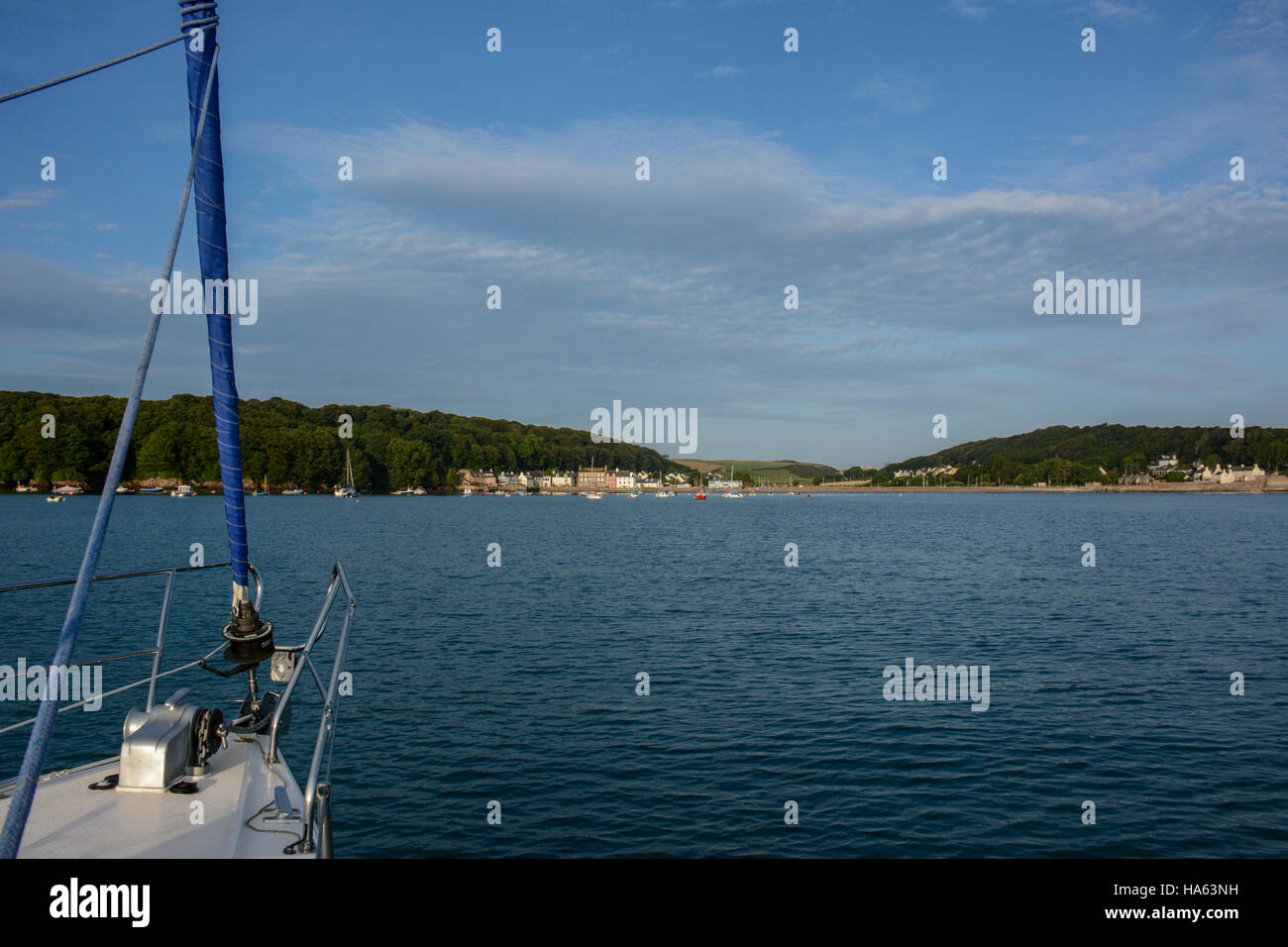 View of Dale village with a yacht's bow anchored in the bay. Blue summer sky with white clouds, blue sea with ripples. Stock Photo