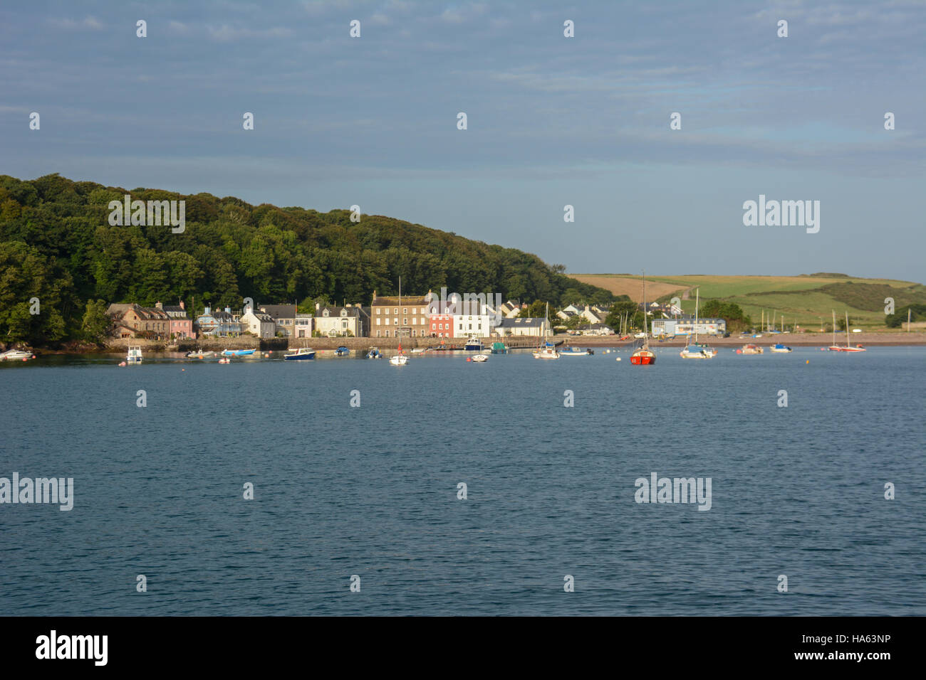 View of Dale village from a yacht anchored in the bay. Blue summer sky with white clouds, blue sea with ripples. - Stock Image