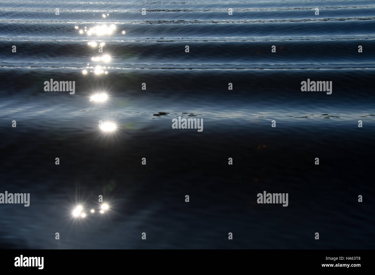 Sunlight making stars on boat wake creating an interesting pattern of waves on blue rippled water. - Stock Image