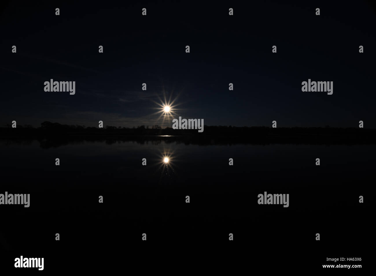 Starry sun reflects in calm water at low tide making a silhouette with deep blue sky - Stock Image