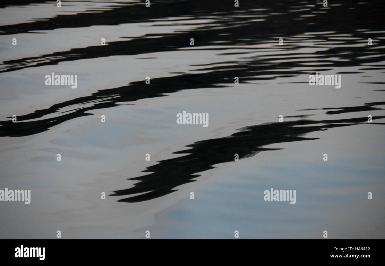 Ripples on water with unusual reflections of black, grey and cyan - Stock Image