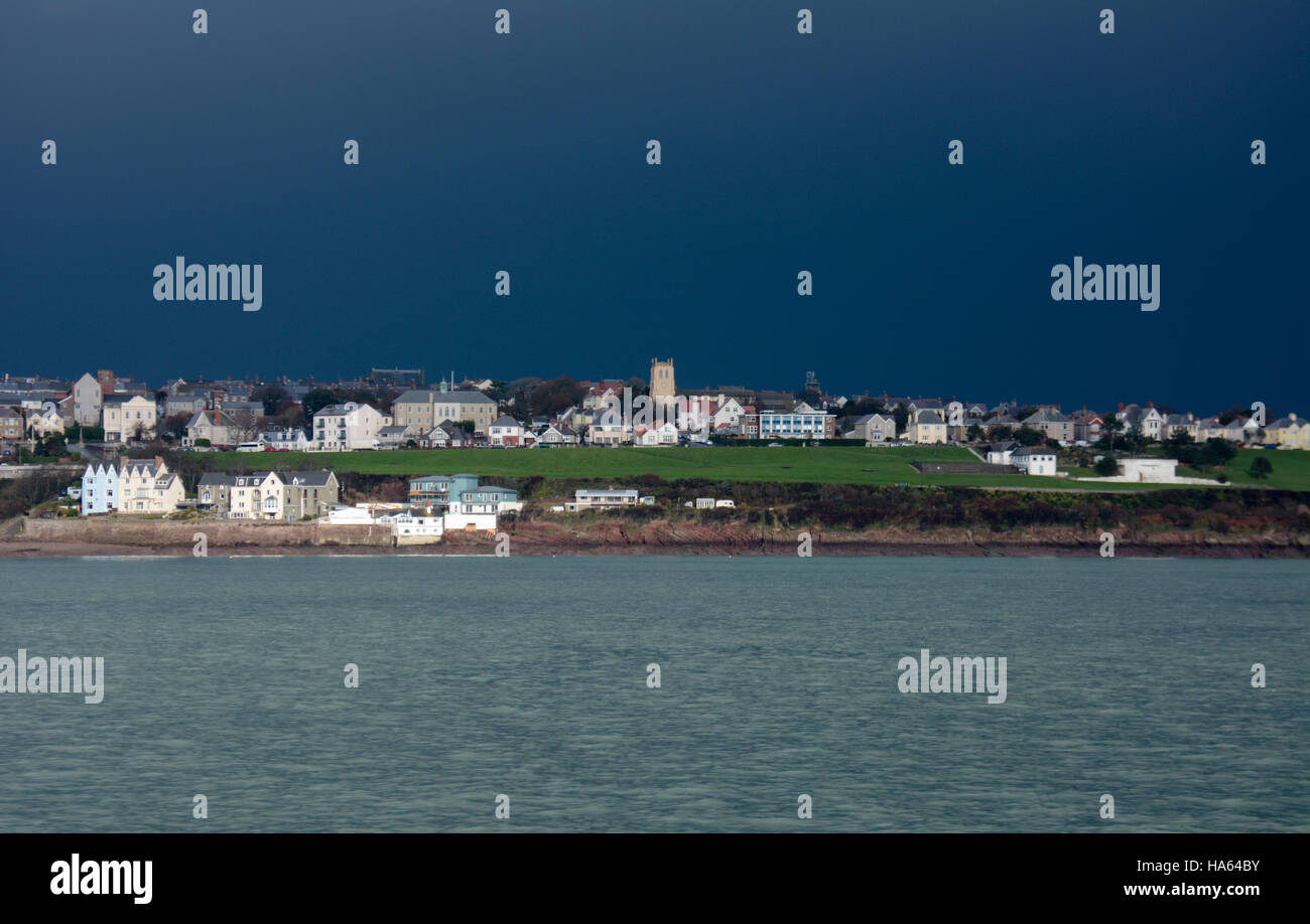 Deep blue stormy sky over Milford Haven with sunlight on church, houses and a patch of bright green grass over a - Stock Image