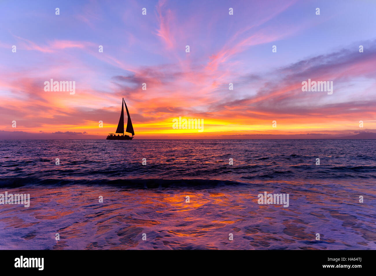 Ocean sunset sailboat silhouette is sailboat sailing along the ocean water with a colorful vivid sunset sky. - Stock Image