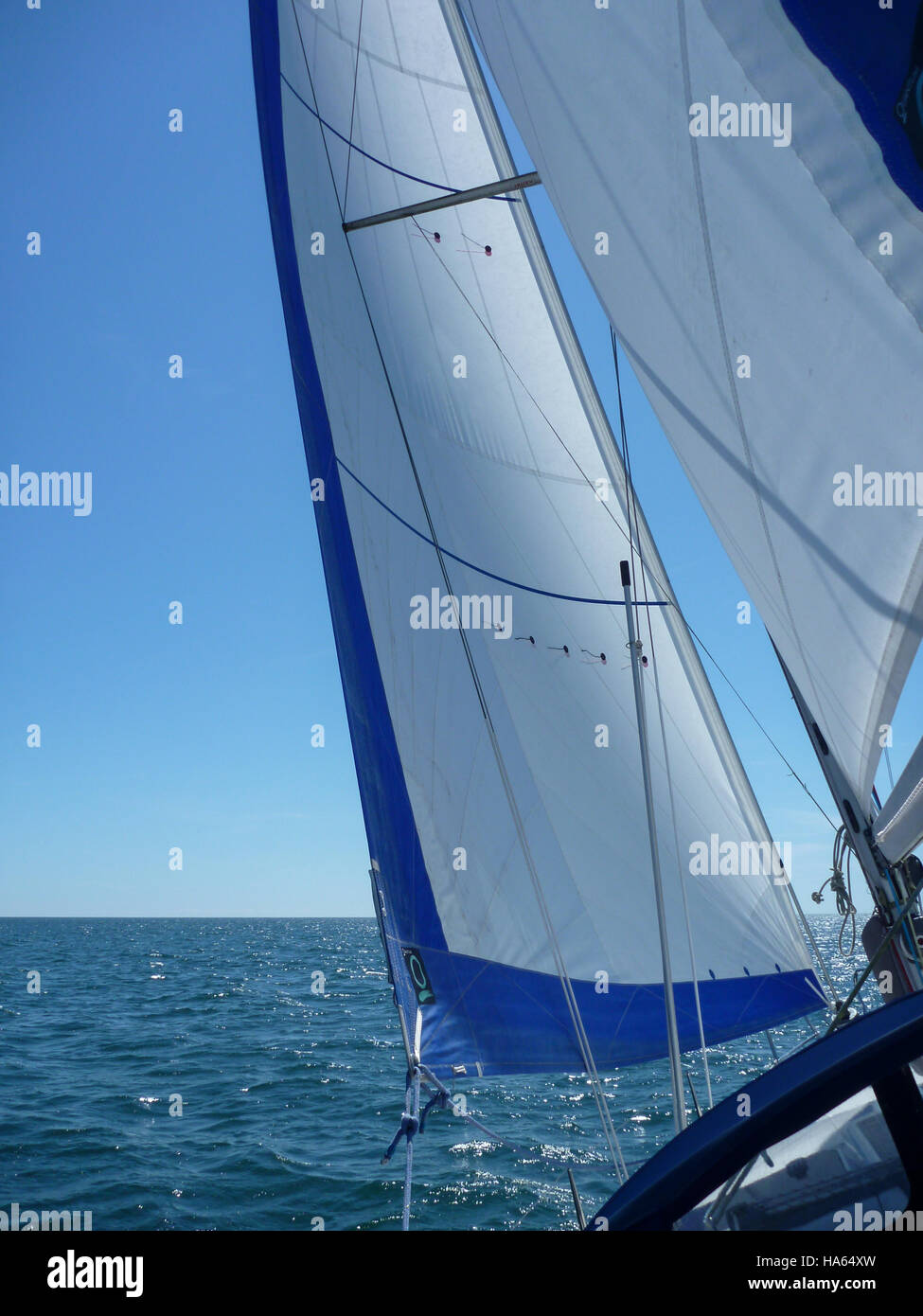 A yacht's foresail and mainsail against a blue sea and blue cloudless sky with telltales flying perfectly. - Stock Image