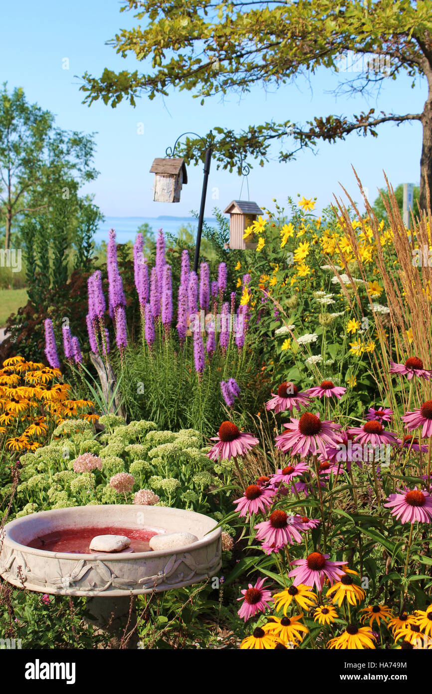 Flower garden with birdbath and birdhouses with Lake Michigan in the ...