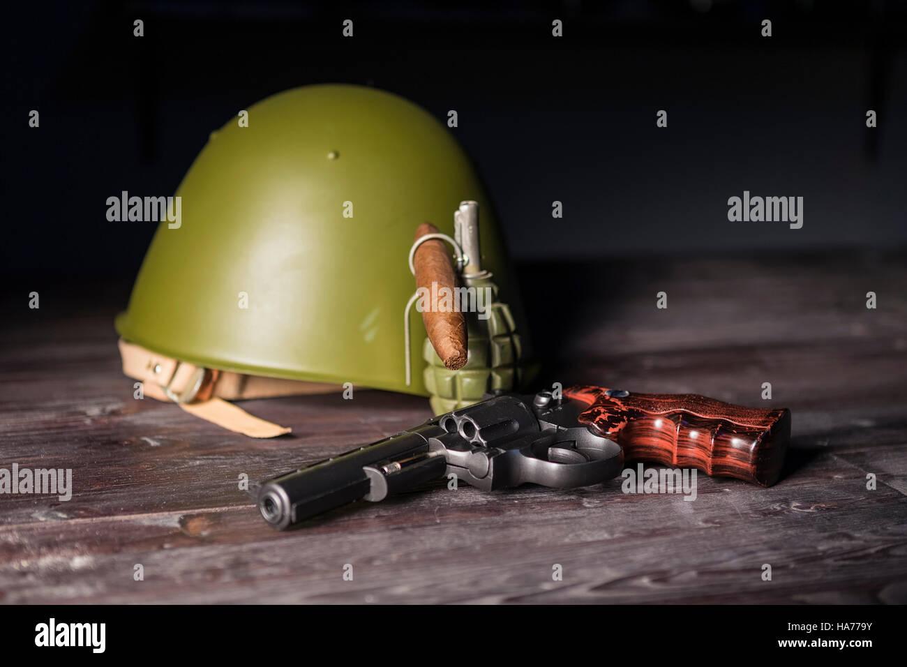 Gun revolver, grenade, protective helmet on the table. - Stock Image