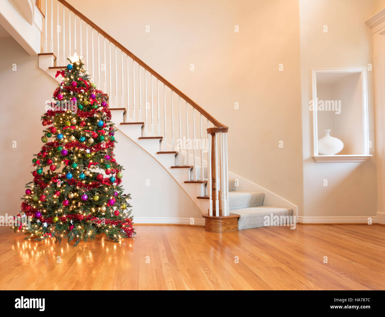 fully decorated christmas on wooden floor with staircase in background stock image - Fully Decorated Christmas Tree