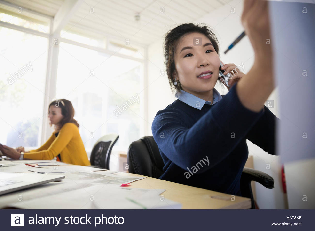 Female architect talking on telephone in office - Stock Image