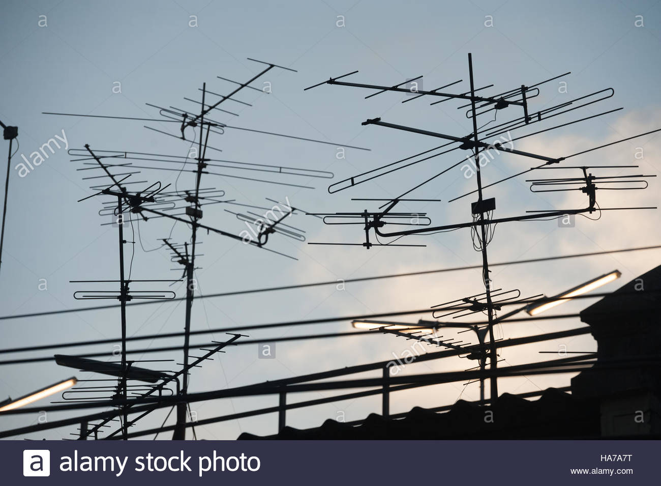 Bangkok Thailand Television aerials silhouetted against the setting sun. - Stock Image