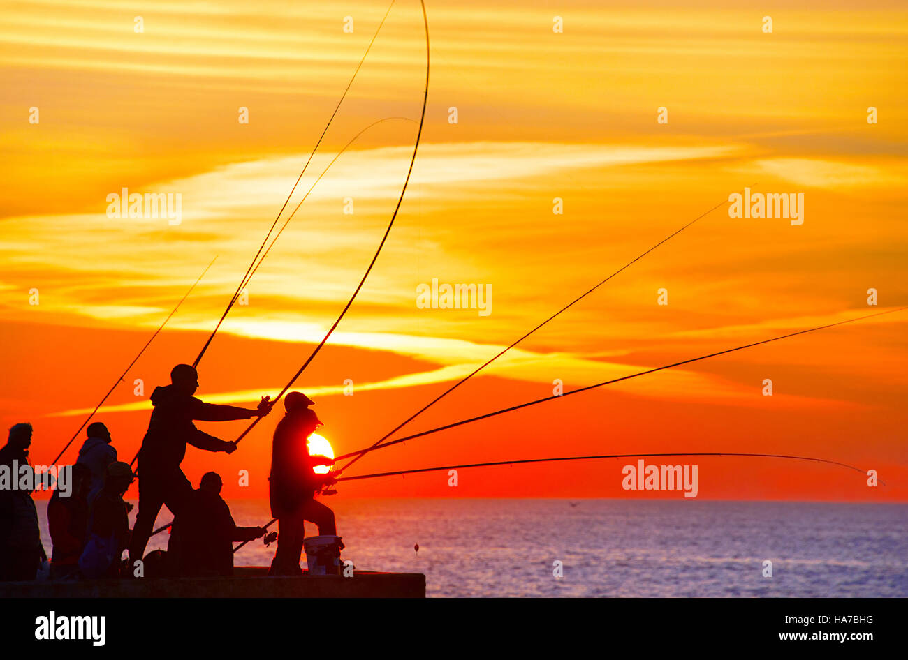 Group of fisherman on a pier at sunset. Porto, Portugal Stock Photo