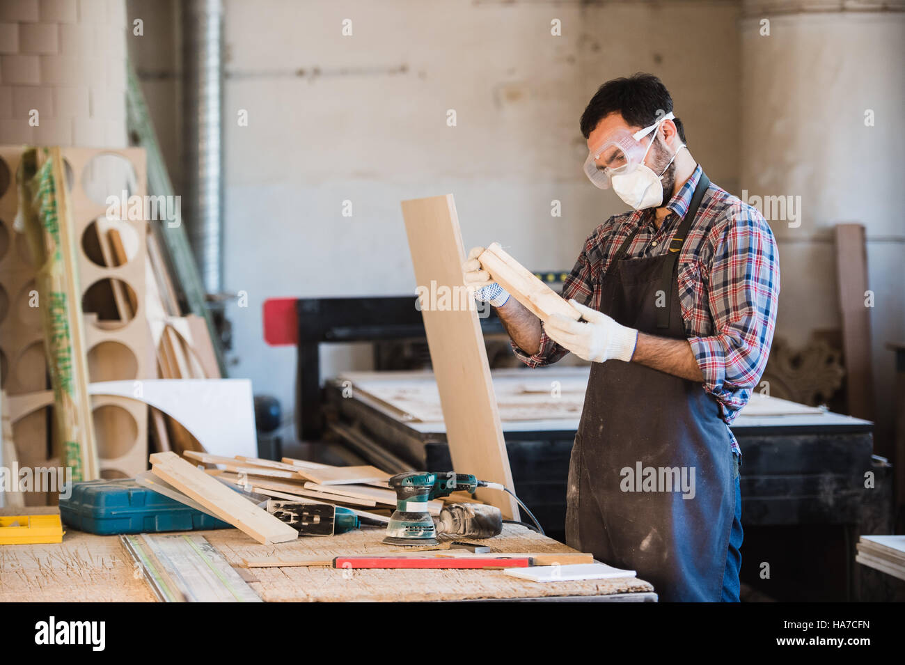 Horizontal view of professionally dressed carpenter varnishing a board - Stock Image