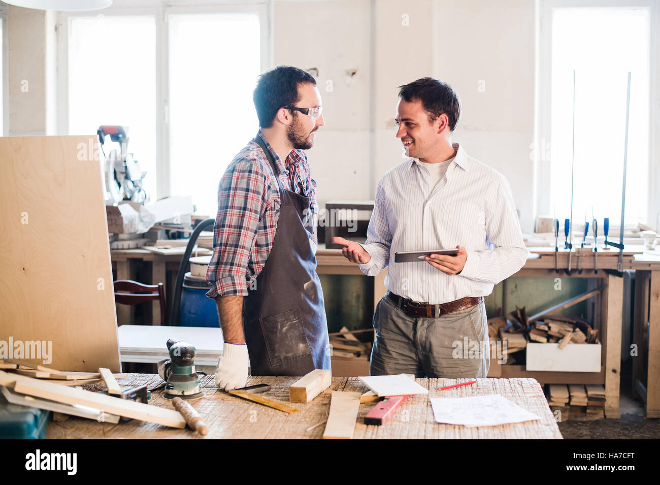 Happy male carpenter showing something to coworker at his notebook papers in workshop Stock Photo