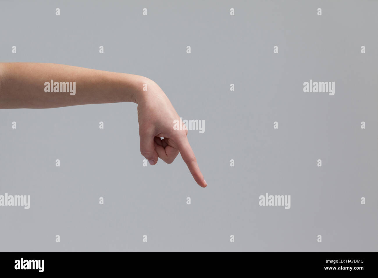 Hand of a woman pointing downwards - Stock Image