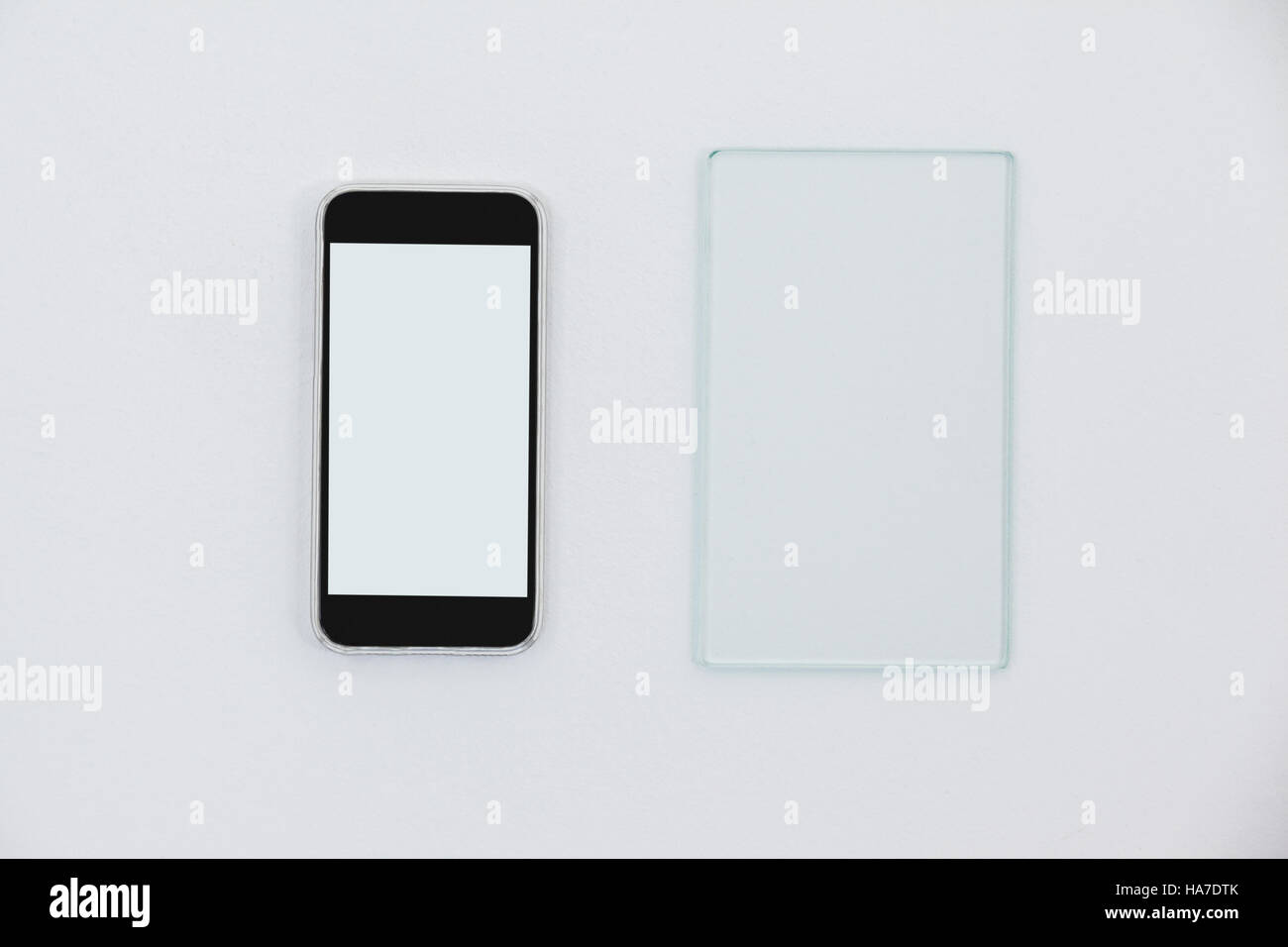 Sheet of glass and mobile phone on white background - Stock Image