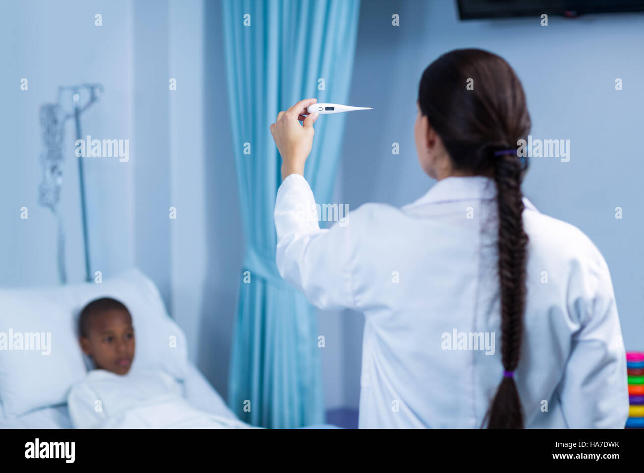 Female Doctor Checking Fever From Digital Thermometer Stock Photo