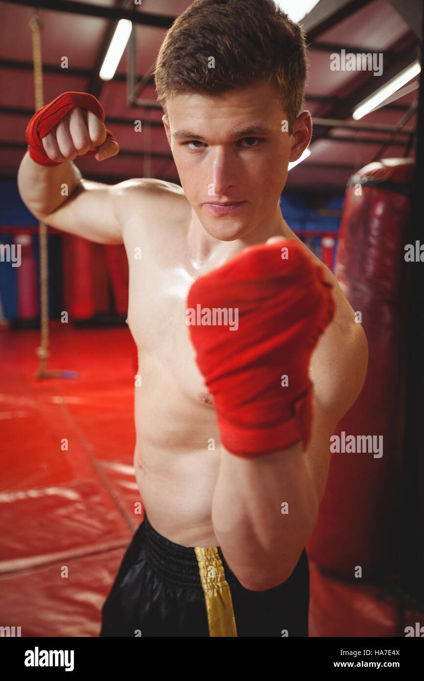 Portrait of a confident boxer punching - Stock Image