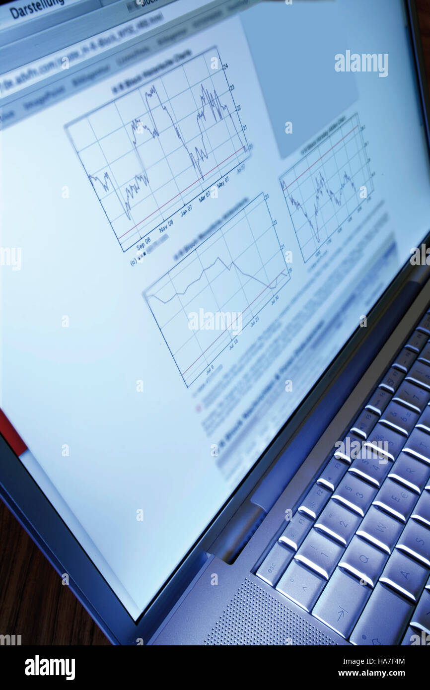 Notebook computer with stock exchange charts - Stock Image