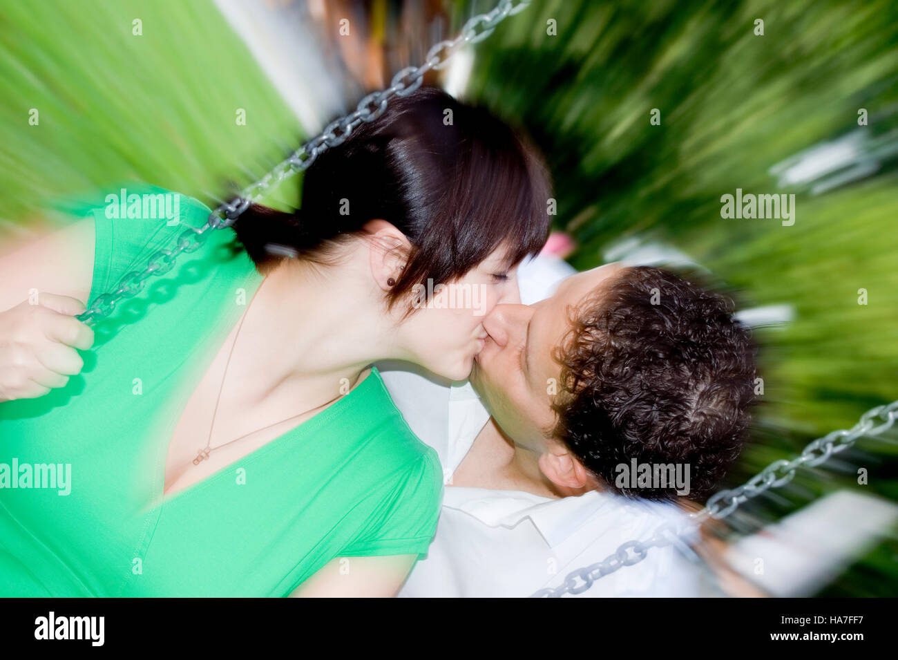 Young woman being kissed by a man while sitting on a swing - Stock Image
