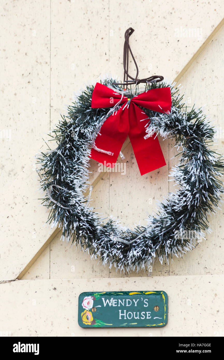 Christmas tinsel wreath with red bow hanging on Wendy's House at Victorian Festival of Christmas at Portsmouth, Stock Photo