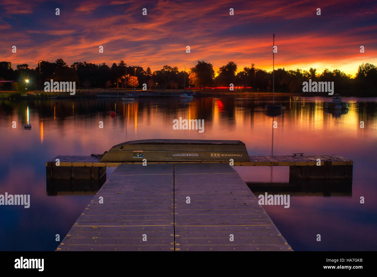 The boat pier at Sloan's Lake in Denver, Colorado awaits visitors as the sunrise paints the sky with incredible Stock Photo