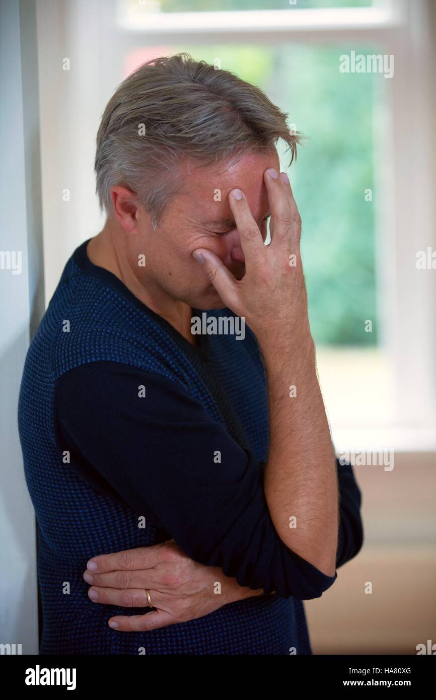 Man with migraine or headache or tired or frustrated - Stock Image