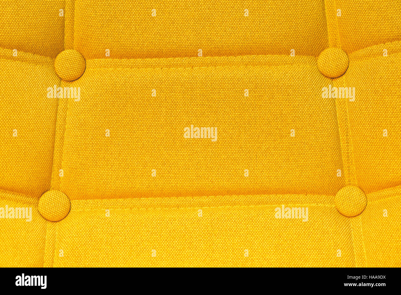 Buttoned chair back support detail, yellow fiber material texture - Stock Image