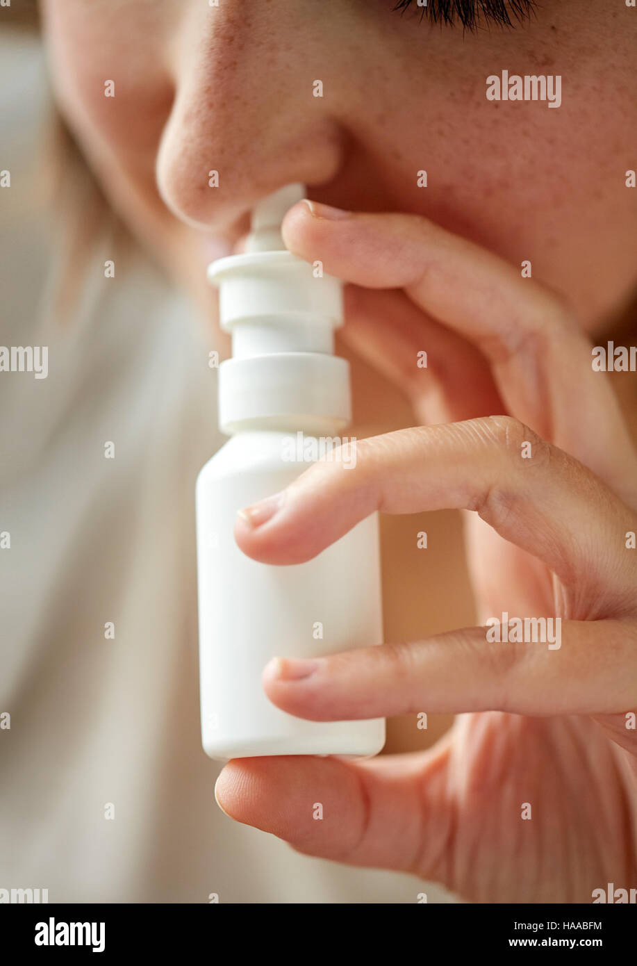 close up of sick woman using nasal spray - Stock Image