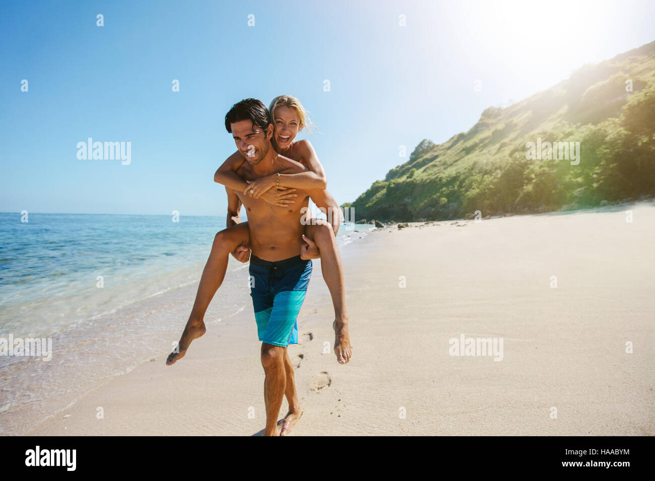 Portrait of man carrying girlfriend on his back along the sea shore. Man giving piggyback ride to girlfriend on - Stock Image