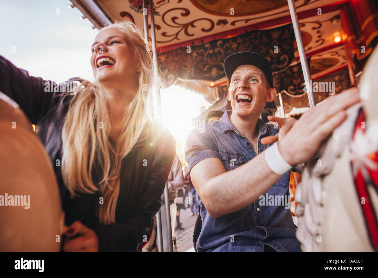 Young man and two women on carousel at fairground. Young couple riding horse carousel in amusement park and laughing. - Stock Image